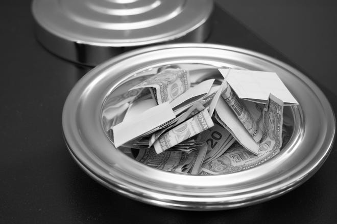 A tithe plate with money in it.