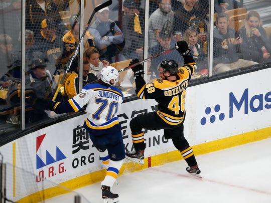 Blues center Oskar Sundqvist boards Bruins defenseman Matt Grzelcyk.