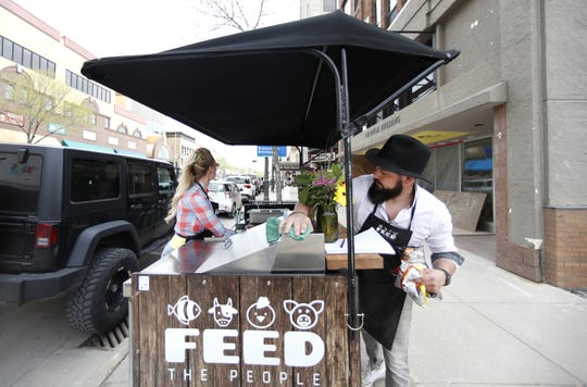 Travis Schinke, right, cleans his food truck in between customers while working the Feed the People grand opening in May.
