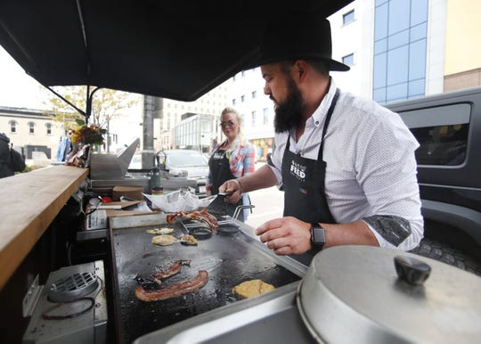 Travis Schinke (right, with Rebecca Martzahl) prepares bacon at his Feed the People food cart in downtown Appleton in May.