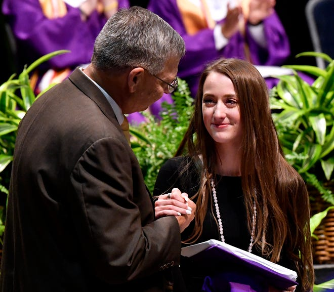 Madison Williams shakes Wylie ISD Superintendent Joey Light's hand after accepting her brother's diploma during commencement at the Taylor County Coliseum Thursday. Dylan Williams is recovering from a car crash and was unable to come to his Wylie High School graduation ceremony. He received a standing ovation from his classmates as his sister walked across the stage for him.