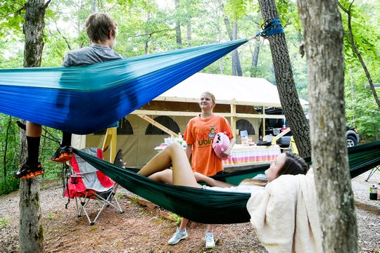 From left, twins Luke and Jordan Halcom, 17, and their sister Joslyn, 21, hang out at their glamping campsite at Lake Powhatan in Asheville May 25, 2019.