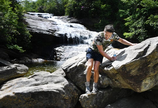 Johnny Quinlan, of Durham, climbs down a rock after cooling off at the bottom of a waterfall at Graveyard Fields on the Blue Ridge Parkway on May 30, 2019.