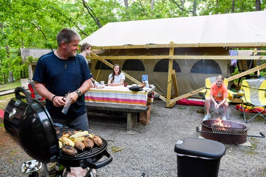 Tommy Halcom grills dinner for his family at their glamping campsite at Lake Powhatan May 25, 2019.