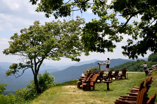 A woman reads the names of the mountains on a sign at the Pisgah Inn on the Blue Ridge Parkway on May 30, 2019.