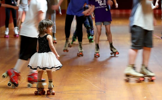 On a pair of tiny roller-skates, two-year-old Savannah Simms watches as the other skaters zoom past her at Skateland in Bremerton on Thursday, May 30, 2019.