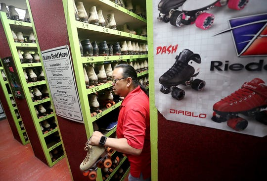 G (the only name anyone knows him by at the rink) grabs a pair of skates from the shelves at Skateland on Thursday. The rink has served as a gathering place for different generations of roller-skaters and has hosted award-winning speed-skating and roller hockey teams.