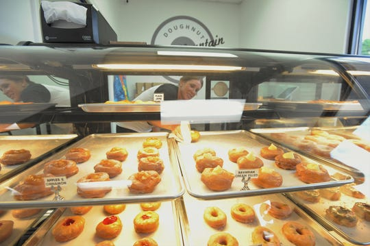 Beckie Davis pulls a Bavarian cream-filled doughnut out of the case at Black Mountain Doughnut Factory on May 30.
