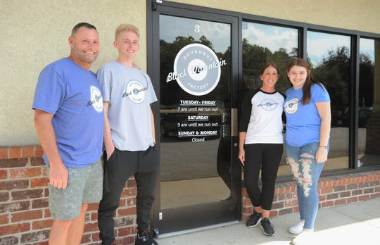 From left to right: Shane, Evan, Beckie and Kiley Davis stand in front of Black Mountain Doughnut Factory, which they opened on May 15.