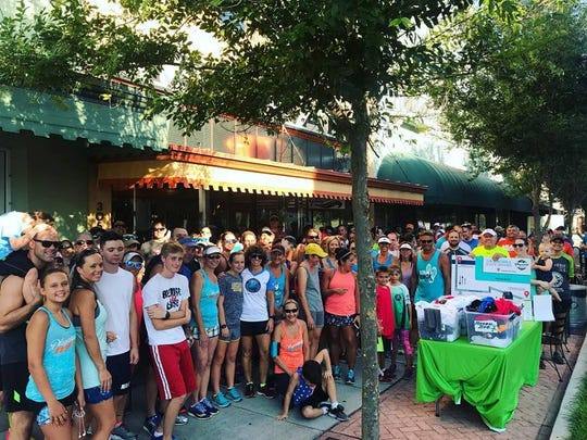 Runners and walkers gather in front of Playalinda Brewing Company's downtown Titusville Hardware Store location at last year's Summer Brewery & Running Tour.