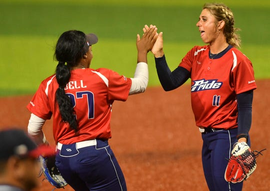 Bianka Bell, left, and former Eau Gallie High standout Alex Powers of the USSSA Pride exchange high fives at the conclusion of a recent exhibition game in Viera.