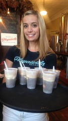 Jayme Hannon of Playalinda Brewing Company holds a tray of root beer floats at the brewery's downtown Titusville location.