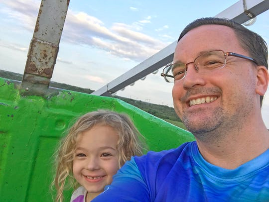 Daddy Duty columnist and his daughter Isabella, 4, enjoy the ferris wheel at the spring fair in Viera.