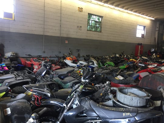 Dozens of confiscated ATVs fill a garage at an impound lot in Pennsauken.
