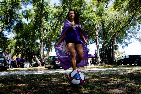 Florencia Gutierrez, of West Palm Beach, plays with a soccer ball while tailgating before the soccer match between FC Cincinnati and Orlando City in a grass lot in the Parramore neighborhood of Orlando, Fla., on May 19, 2019. Gutierrez traveled the 170 miles from West Palm Beach to Orlando for the soccer game between FC Cincinnati and Orlando City.