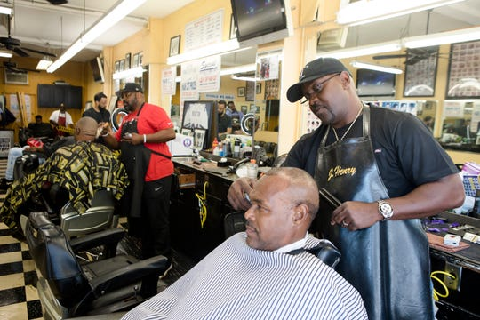 J Henry, owner of J Henry's barber shop, cuts Jay Glovers hair on May 18, 2019, in Orlando, Fla. The barber shop sits directly across the street from Orlando City Stadium.
