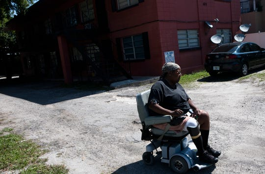 Mattie Thornton rides in front of her apartment building in the Parramore neighborhood of Orlando, Fla., on May 18, 2019. Thornton said her rent had been raised twice since she moved in three years ago.