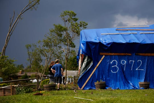 Rachel and Jeff Fogle look over the damage to their home on La Bonne Street in Beavercreek, Ohio, on Friday, May 31, 2019. The Fogles, who are expecting the birth of their son in July, were in their home when the tornado struck it, tearing the roof from the structure and damaging their property. The couple took shelter in their basement as emergency alerts warned them of the nearing storm.