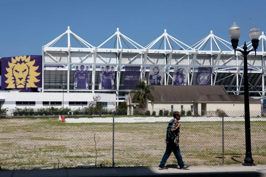 A pedestrian walks down South Terry Avenue on the east side of Orlando City Stadium in Orlando, Fla., on May 18, 2019.