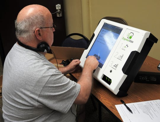 Dave Eckley of Election Systems and Software tests and ExpressVote machine received recently by the Coshocton County Board of Elections. The new machines will be used for the fall general election.