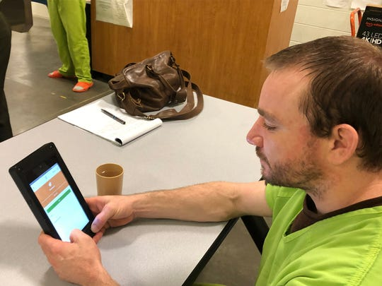 Gary Sawyer, 35, checks emails on a tablet at the Polk County Jail. A phone call costs 15 cents a minute, an email 9 cents and a videoconference costs $11.99.