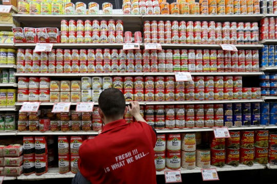Moses Konja, 28 of Warren and a receiving and stocking worker at Prince Valley Supermarket on Michigan Avenue in Detroit, organizes an entire aisle of made in Mexico canned goods from beans to mole sause, rice to pasta at the store on Friday, May 31, 2019.
