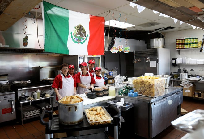 Some of the kitchen staff that makes hot food for sale at Prince Valley Market & Bakery on Michigan Avenue in Detroit pose for a picture while taking a break from making tamales.
