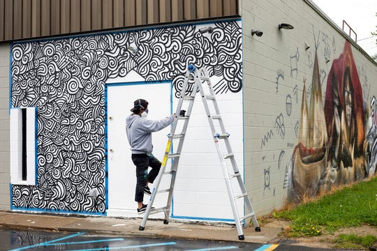 Artist Simo Vibart, from Argentina, creates a mural on the outside of Totem Books in downtown Flint, Mich., on Thursday, May 30, 2019. Artists from around the world are joining Michigan artists in painting 50 murals throughout Flint as part of an effort to refocus the city's image on art rather than the lead-tainted water crisis.