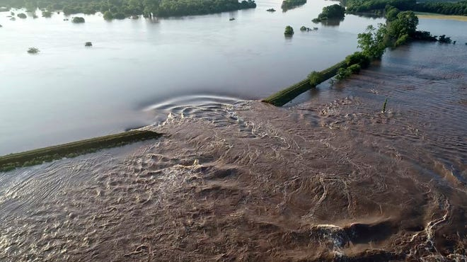 In this aerial image provided by Yell County Sheriff's Department water rushes through the levee along the Arkansas River Friday, May 31, 2019, in Dardanelle, Ark. Officials say the levee breached early Friday at Dardanelle, about 60 miles northwest of Little Rock.  ( via AP)