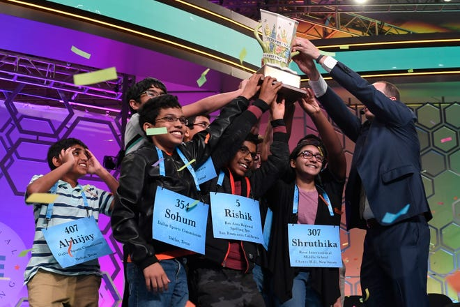 Abhijay Kodali, 12, of Flower Mound, Texas; Sohum Sukhatankar, 13, of Dallas; Rishik Gandhasri, 13, of San Jose, Calif.; Shruthika Padhy, 13, of Cherry Hill, N.J., and the other winning spellers gather at the end of the 2019 Scripps National Spelling Bee in Oxon Hill, Md., early Friday, May 31, 2019. The bee ended in an unprecedented 8-way championship tie.