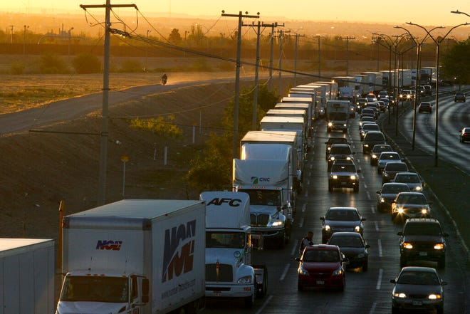 In this April 9, 2019, file photo, trucks wait to cross the border with the U.S. in Ciudad Juarez, Mexico.  In a surprise announcement that could compromise a major trade deal, President Donald Trump announced Thursday that he is slapping a 5% tariff on all Mexican imports to pressure the country to do more to crack down on the surge of Central American migrants trying to cross the U.S. border.