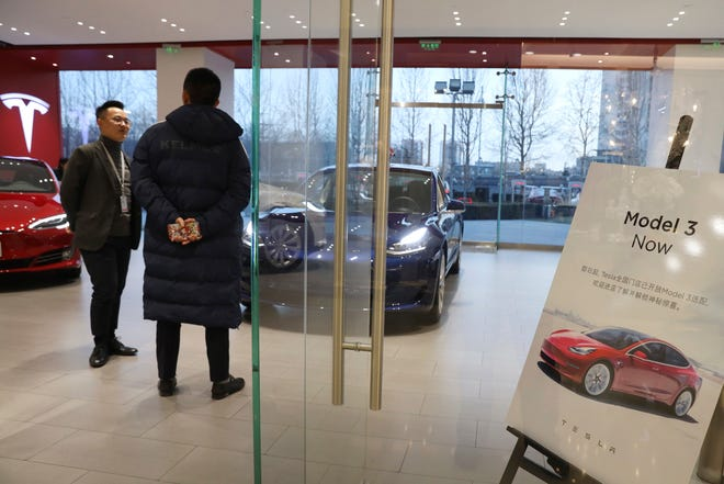 A customer eyes a Tesla Model 3 in Beijing, China, Monday, Jan. 7, 2019. Tesla has started taking orders for the Model 3 cars it will make in China, its second-largest market, and lowered the price of the vehicle, according to a statement Friday, May 31, 2019.