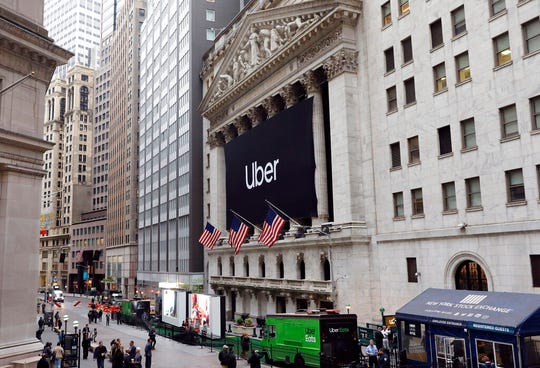 In this May 10, 2019, file photo, an Uber banner hangs on the facade of the New York Stock Exchange. Uber is continuing to bleed money even as it posts dramatic revenue growth. In its first financial release since its lackluster IPO, Uber reported Thursday, May 30, that revenue rose in the first quarter of 2019, up 20% from the same time last year.