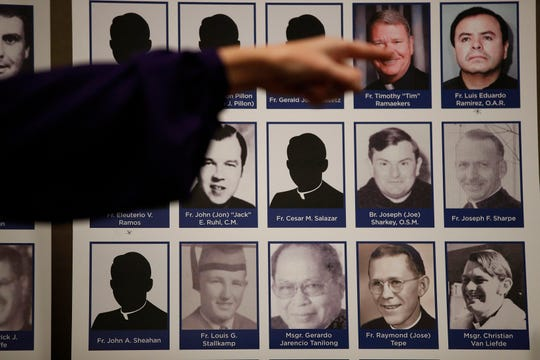 In this Thursday, Dec. 6, 2018 file photo, a sexual abuse victim points to the photos of Catholic priests accused of sexual misconduct by victims during a news conference in Orange, Calif.