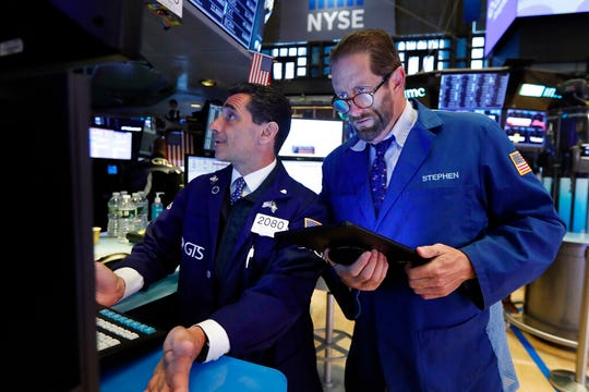 In this May 28, 2019, file photo specialist Peter Mazza, left, and trader Stephen Gilmartin work on the floor of the New York Stock Exchange. The U.S. stock market opens at 9:30 a.m. EDT on Friday, May 31.