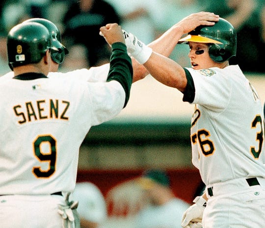 Oakland Athletics' Jason Giambi and Olmedo Saenz congratulate rookie Adam Piatt on a home run in the third inning against the Boston Red Sox at the Coliseum Saturday evening in 2000.