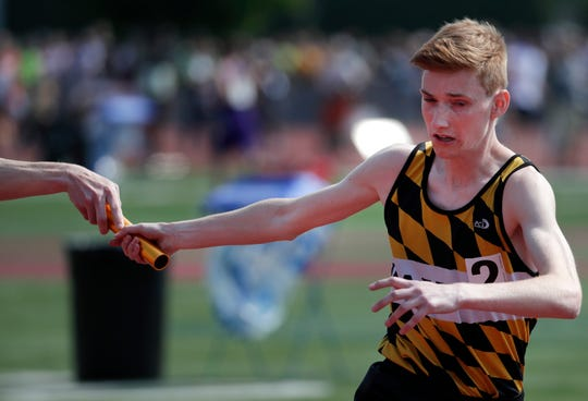 Waupun's Adam Vanderkin takes the baton while running in the Division 2 3,200 relay during the WIAA state track and field meet Friday at Veterans Memorial Field Sports Complex in La Crosse.