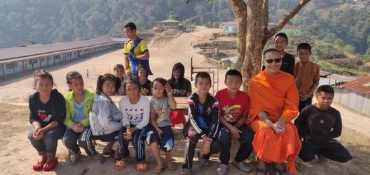 Phra Ajahn Duke Palacios sits with some of the young students at Shan State National School in Myanmar.