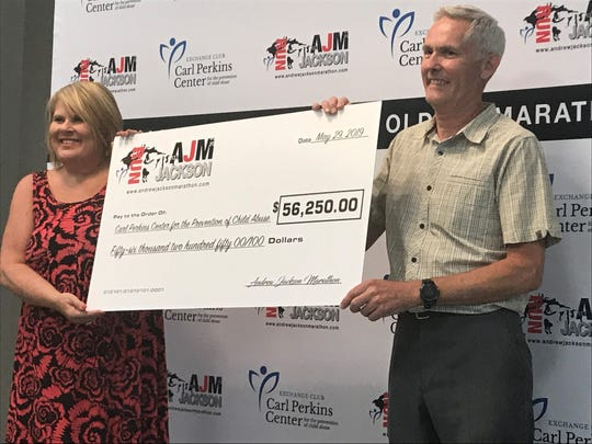 Danny Crossett presents a check to Pam Nash and the Carl Perkins Center for the Prevention of Child Abuse on behalf of the Andrew Jackson Marathon.
