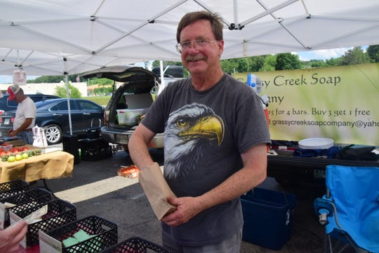 Lance Davis from Grassy Creek Soap bags soap made from an old timey lye recipe at the Hardin Valley FARM Market. 5/29/19