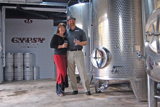 Stephanie and Aaron Carson pose next to their fermentation tanks at Gypsy Circus Cider Company in Kingsport.
