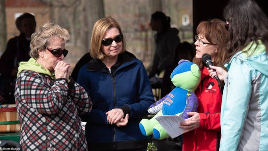"Karen Rau, Marshfield Area Pet Shelter executive director, is pictured holding and presenting a special ""memory bear"" to the family of Duane Kulke, one of the founders of Paws For Brittany who passed away earlier this year. This special tribute kicked-off this year's event on May 11 at Wildwood Park & Zoo. Pictured from left to right with Rau are Duane's family, who were attending this year's event, Beverly Kulke, Duane's mother, Wendy Hiltunen, his significant other, and Aubrey Kulke, Duane's daughter-in-law, pictured at far right."