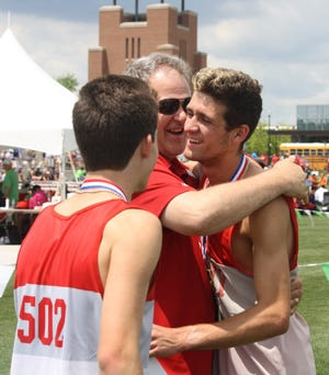 Shelby High School principal John Gies congratulates Sam Logan after the Whippets win a Division II state championship in the 4x800 relay at the 2019 state track and field meet.