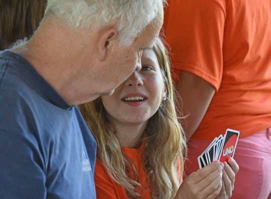 Sherman Elementary student Hayden Smith enjoys a game of Uno with Dayspring Assisted Living resident Woody Hill on Friday during a picnic.
