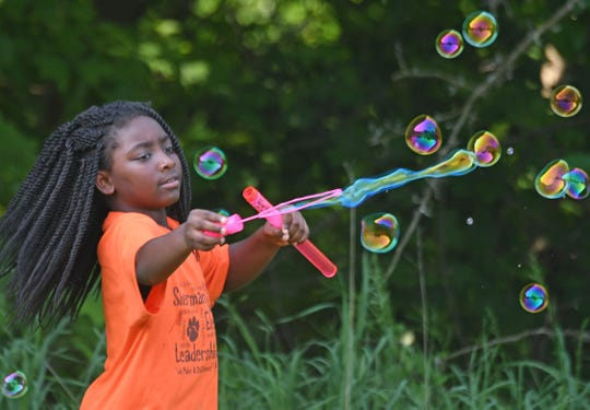 Cordelia Pinkston-Spicer of Sherman Elementary plays with bubbles on Friday during a cookout at Dayspring Assisted Living.