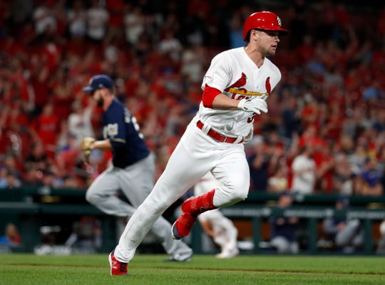 kSt. Louis Cardinals' Lane Thomas, right, heads to first after hitting a two-run single off Milwaukee Brewers relief pitcher Aaron Wilkerson, left, during the seventh inning of a baseball game Monday, April 22, 2019, in St. Louis. (AP Photo/Jeff Roberson)