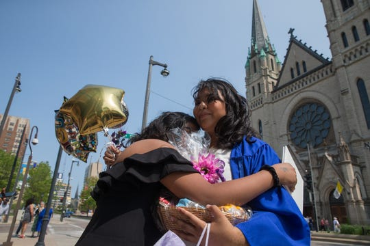 Maria Torres, 17, embraces her younger sister Brianna Torres, 11, telling her not to cry just after graduating from Cristo Rey Jesuit High School at the Church of the Gesu at Marquette University on Friday. Maria Torres is among 84 other students at Cristo Rey who mark the first graduating class for the Milwaukee High School.