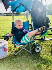 Teddy Fletcher, 2, kicks back with a drink at the ballpark.
