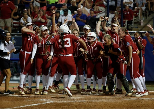 Claire Jenkins reaches home plate to be greeted by her teammates after hitting a solo home run to tie the score against Oklahoma at 2-2 on Thursday in the Women's College World Series.