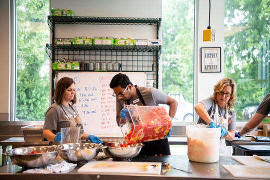 Kim Cammuse, Vikram Bollu and Cathy Morgan, from left, make a fruit salad during food prep at the Nashville Food Project on May 30, 2019.